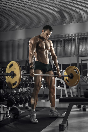 guy bodybuilder, perform exercise with weights barbell, in dark gym