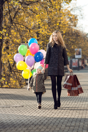 happy woman and little child with red shopping bag and air-balloons, walking on street Stock Photo