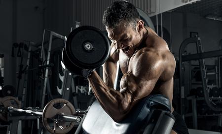 guy bodybuilder , perform exercise with dumbbells, in dark gym