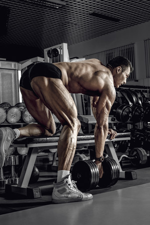 guy bodybuilder, perform exercise with dumbbell on broadest muscle of a back, in dark gym Stock Photo