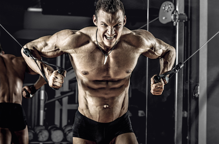 guy bodybuilder, perform exercise with exercise machine crossover, in gym Stock Photo