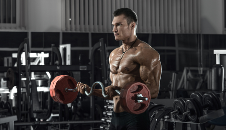 guy bodybuilder, perform exercise with barbell, in dark gym Stock Photo