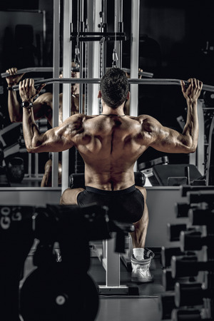 guy bodybuilder, perform exercise with exercise machine on broadest muscle of a back, in dark gym