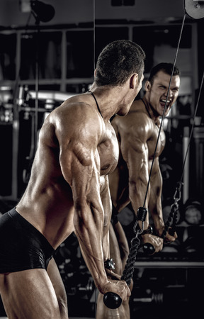guy bodybuilder, perform exercise with exercise machine on triceps, in dark gym