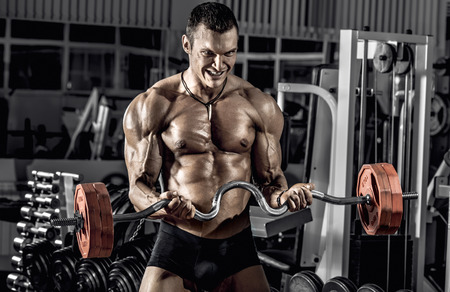 guy bodybuilder, perform exercise with weights barbell, in gym Stock Photo