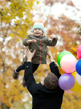 happy father toss up little child with air-balloons, outing in autumn park