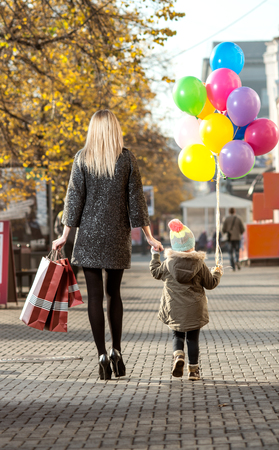 woman and little child with red shopping bag and air-balloons, walking on street