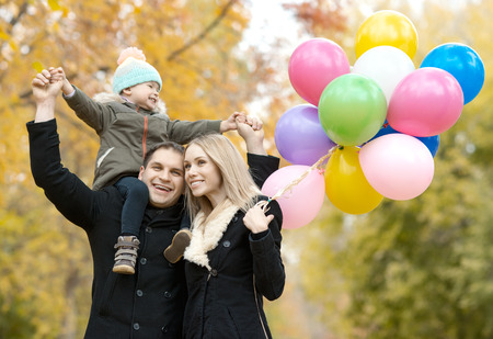 happy family with little child and air-balloons, outing in autumn park Stock Photo