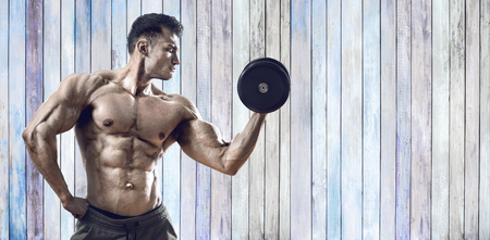 guy bodybuilder, perform exercise with dumbbell on background of old wood plank Stock Photo