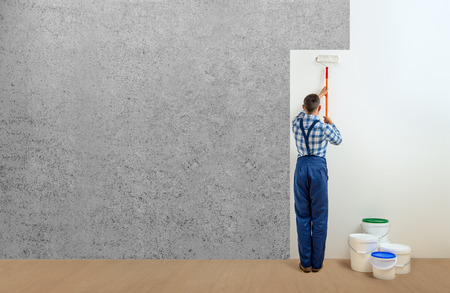 worker - painter with tool in the white room. Walls painting concept