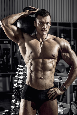guy bodybuilder, perform exercise with weight, in gym Stock Photo