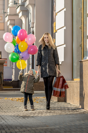 happy woman and little child with red shopping bag and air-balloons, walking on street Reklamní fotografie