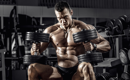 guy bodybuilder, perform exercise with dumbbell, in dark gym
