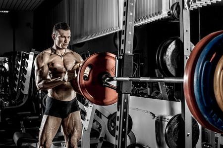 guy bodybuilder equip barbell, in dark gym