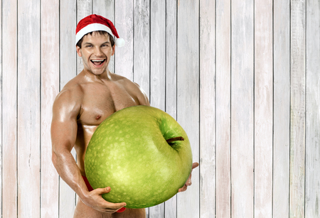 fitness Santa Claus hold great green apple and laughing