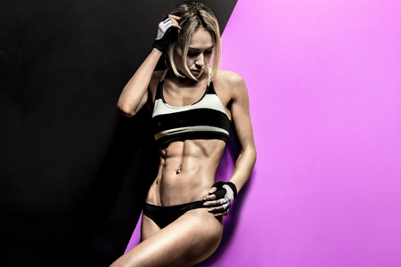 young fitness woman in swimsuit on black and mauve background, horizontal photo Reklamní fotografie