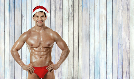 muscular handsome sexy Santa Claus, on background of old wood plank
