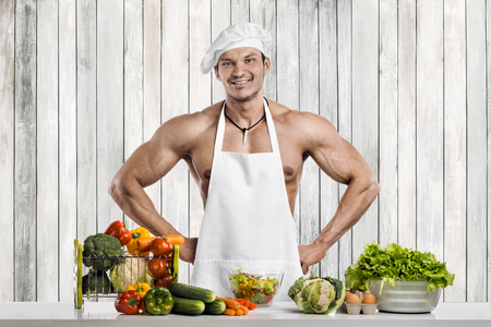 Man bodybuilder on kitchen in white toque blanche and cook protective apron, concoction vegetables and smile Reklamní fotografie