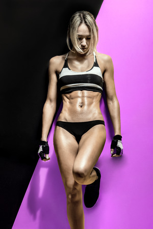 young fitness woman in swimsuit on black and mauve background, vertical photo
