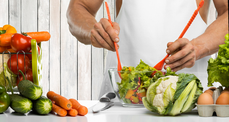 man hand cook make mix vegetables salad on kitchen, closeup photo