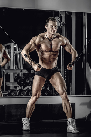 guy bodybuilder, perform exercise with exercise machine crossover, in gym Reklamní fotografie