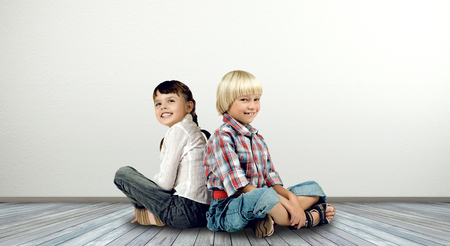 two little children sitting back to back and smile, in empty room on floor Reklamní fotografie