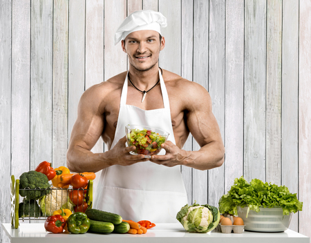 Man bodybuilder in white toque blanche and cook protective apron, concoction vegetables and fruit