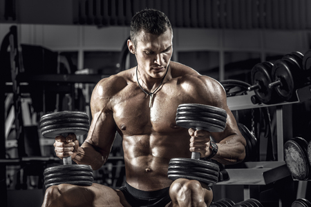 guy bodybuilder, perform exercise with dumbbell, in dark gym