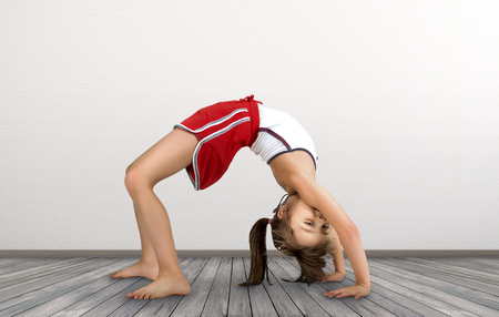 little girl doing exercises gymnastic bent back, in empty room on floor