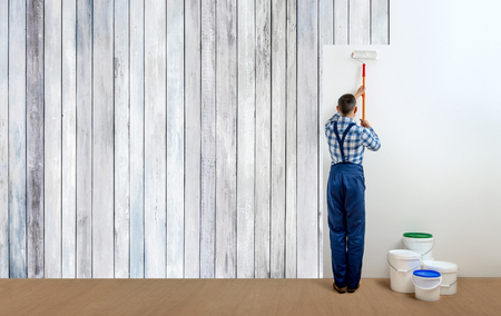 man worker - painter with tool in the white room. Walls painting concept