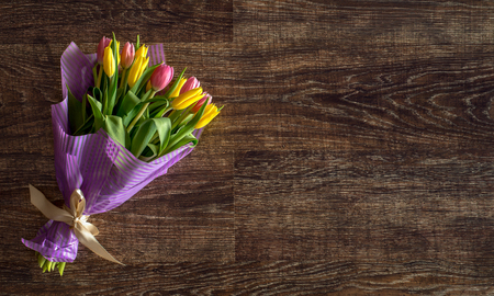 bouquet of yellow tulips on old wood board background, still-life, horizontal photo Reklamní fotografie