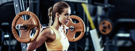 young fitness woman execute exercise with barbell in gym, horizontal photo Reklamní fotografie
