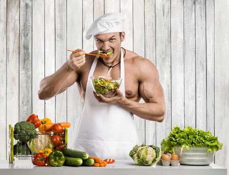 Man bodybuilder on kitchen in white toque blanche and cook protective apron, concoction vegetables and fruit