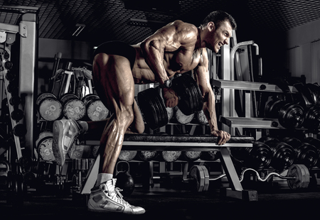 guy bodybuilder, perform exercise with dumbbell on broadest muscle of a back, in dark gym Reklamní fotografie