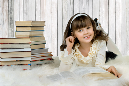 beautiful little girl lie with textbook and happy smile Reklamní fotografie