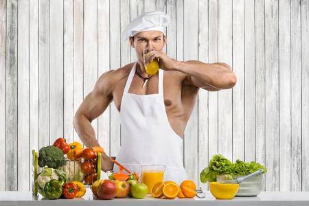 Man bodybuilder cook, cooking on kitchen freshly squeezed juice and vegetables salad Reklamní fotografie