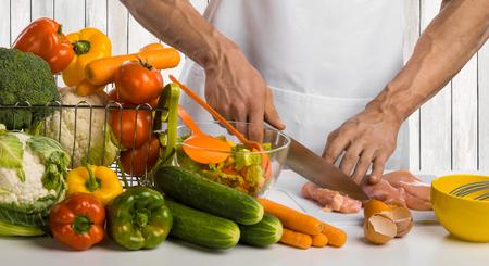 man hand cook cut chicken meat ( chicken breast) and salad on kitchen, closeup photo