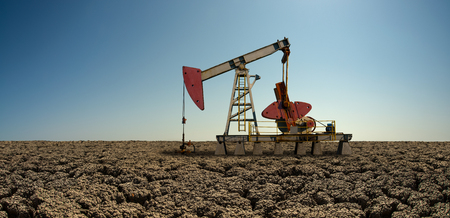 oil derrick pumping crude in droughty desert , oil-extracting industry concept, horizontal photo