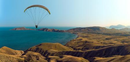 flying on paraplane on beauty landscape background, extreme rest сoncept, horizontal photo