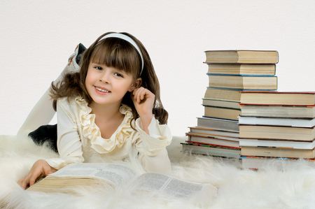 beautiful little girl lie with textbook and happy smile, on white background Reklamní fotografie