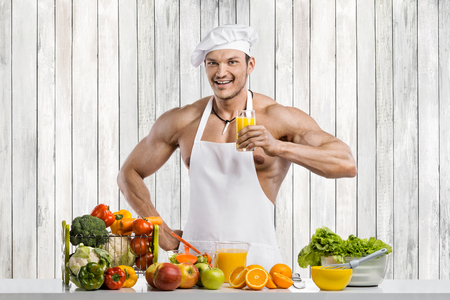 Man bodybuilder cook, cooking freshly squeezed juice and vegetables salad on kitchen