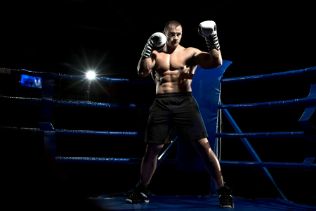 boxer on boxing ring, black background, horizontal photo
