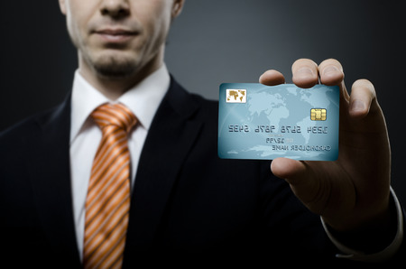businessman in black costume and orange necktie reach out on camera and show credit card, close up Reklamní fotografie