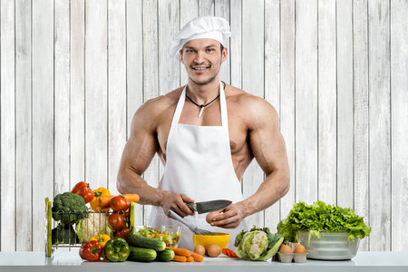 Man bodybuilder cooking on kitchen in white toque blanche and cook protective apron