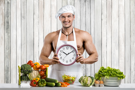 Man bodybuilder cooking on kitchen in white toque blanche and cook protective apron with clock