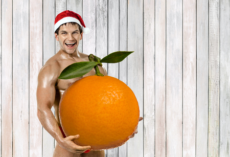fitness Santa Claus hold great orange tangerine and laughing Stock Photo