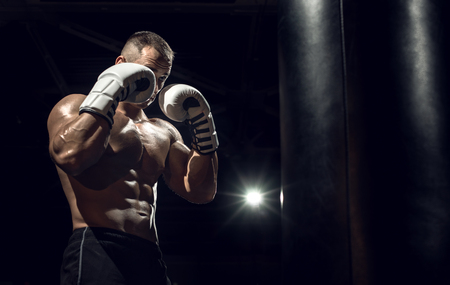 boxer in gym with boxing gloves, safeguard stand, black background, horizontal photo