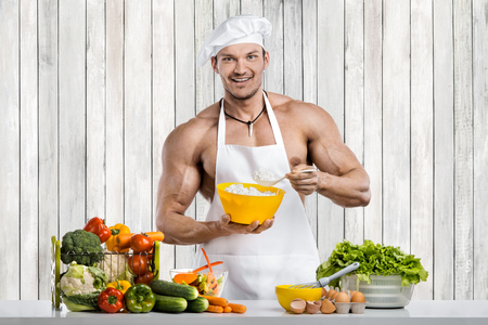 Man bodybuilder on kitchen in white toque blanche and cook protective apron cooking cottage cheese and vegetables