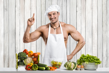Man bodybuilder in white toque blanche and cook protective apron cooking on kitchen