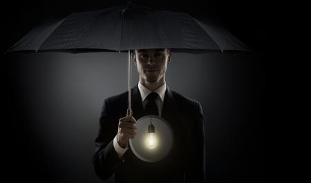 man in black costume with umbrella, shine bulb instead of soul Reklamní fotografie
